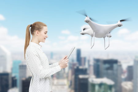 Side view of a beautiful businesswoman in a polka shirt looking at her tablet screen and navigating a quadcopter in a city.