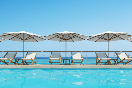 cloudless: White deck chairs are standing under beach umbrellas near a swimming pool. A blue cloudless sky is above them. Close up. 3d rendering mock up