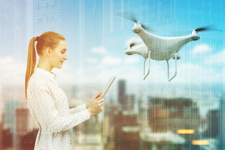 Side view of a beautiful businesswoman in a polka shirt looking at her tablet screen and navigating a quadcopter in a city. Toned image double exposure