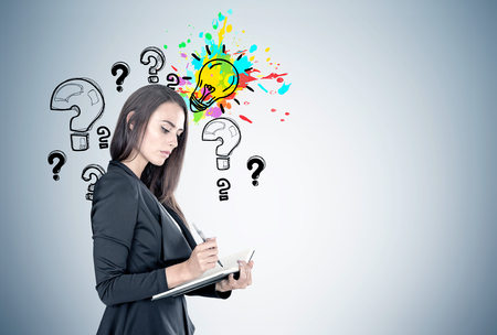 Portrait of a beautiful young businesswoman wearing a black suit and holding a planner and a pen taking notes. Gray wall with question marks and a colored light bulb. Mock up