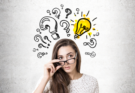 Young woman wearing white sweater and holding her glasses with thick frame. She is looking to the distance while standing near a concrete wall with a colorful light bulb and question marks Stock Photo