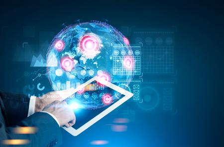 Close up of a hand of a man holding a tablet computer and interacting with graphs, HUD and holograms. Mock up toned image double exposure. Elements of this image furnished by NASA