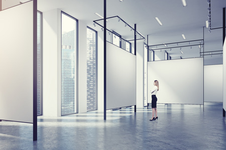 showpiece: Art gallery with blank walls with special lightning, a magnificent cityscapes with skyscrapers white ceiling and a concrete floor. Blonde woman. 3d rendering mock up Stock Photo
