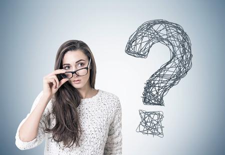 Jonge vrouw met donker lang haar draagt een witte trui en houdt haar bril met een dik frame. Ze kijkt naar de afstand terwijl hij zich bij een grijze muur bevindt met een vraagteken