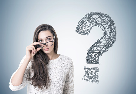 Young woman with dark long hair is wearing a white sweater and holding her glasses with a thick frame. She is looking to the distance while standing near a gray wall with a question mark Foto de archivo