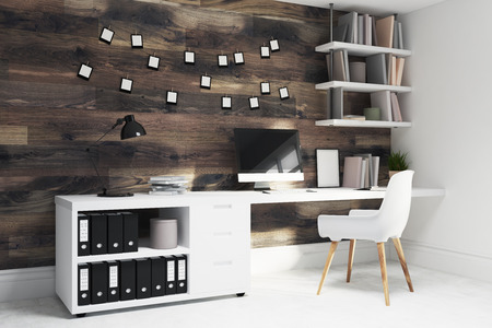 interior decoration: Dark wooden wall home office with a wooden floor, a desktop and a white chair near a computer table. Bookshelves, side. 3d rendering mock up
