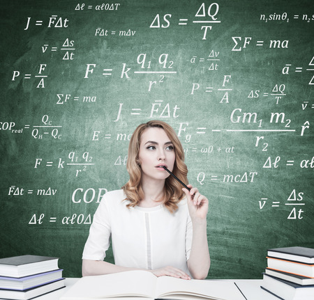 formula one: Portrait of a gorgeous young businesswoman with red hair wearing a black suit and a white shirt and holding an open copybook. She is thinking and biting a pencil. Blackboard with formulas on it.