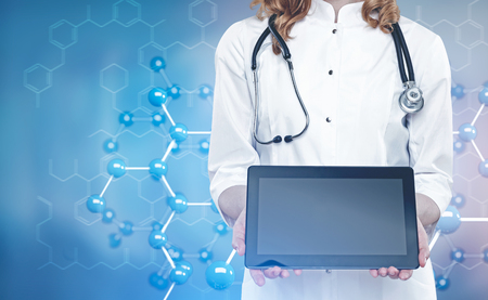 commercial medicine: Close up of an unrecognizable woman doctor holding a tablet computer with a blank screen. Blurred background with an atomic grid. Toned image double exposure mock up