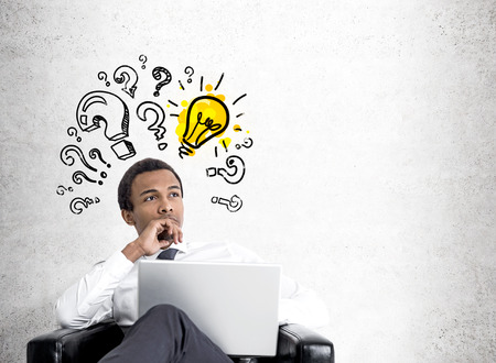 Close up of a young African American businessman sitting in a large black armchair with a laptop and looking to the distance. Concrete wall with a yellow light bulb and question marks. Mock up