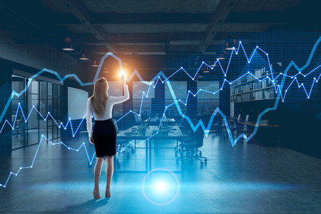 Rear view of a blonde businesswoman drawing a holographic diagram in an office at night. Toned image double expsoure mock up