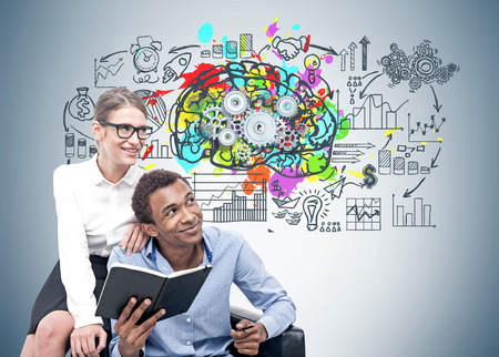 Smiling African American businessman and his blonde colleague in glasses sitting in an armchair near a gray wall with a colorful brain sketch and gears on it 스톡 콘텐츠