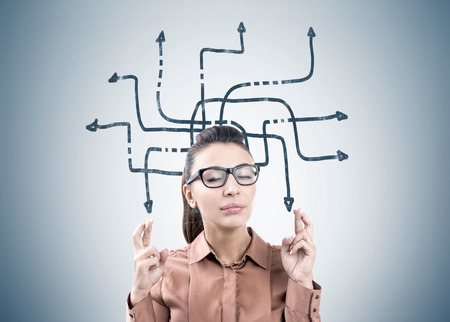 Portrait of a young businesswoman wearing a brown blouse and glasses and standing with closed eyes and crossed fingers near a gray wall with an arrow labyrinth on it. Stock Photo