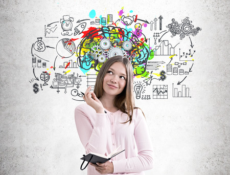 Portrait of a dreamy girl in a pink sweater holding a planner and a pen and standing near a concrete wall wall with a colorful brain sketch and gears on it and a business scheme Stok Fotoğraf