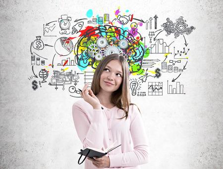 Ritratto di una ragazza sognante in un maglione rosa in possesso di un pianificatore e di una penna e in piedi vicino a un muro di cemento parete con un schizzo cervello colorato e ingranaggi su di esso e uno schema di business Archivio Fotografico - 85098864