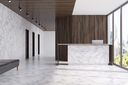 Marble reception table with a computer on it standing near a dark wooden wall fragment in a marble office. Loft windows. 3d rendering mock up Stok Fotoğraf