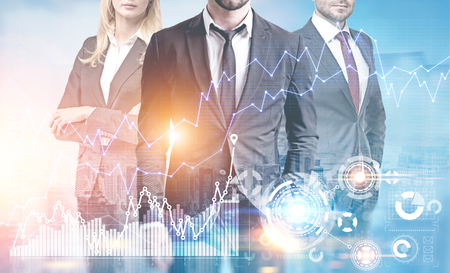 Unrecognizable business team members are standing against a cityscape. There are graphs and HUD in the foreground. Toned image double exposure