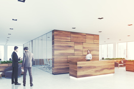 Side view of a wooden reception desk standing in an open space
