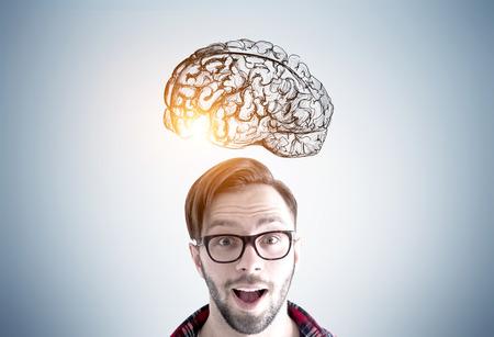 Schließen Sie oben von einem erstaunten jungen Mann, der Brille trägt und steht mit einem geöffneten Mund nahe einer grauen Wand mit einer Gehirnskizze, die darauf gezeichnet wird. Getöntes Bild Standard-Bild