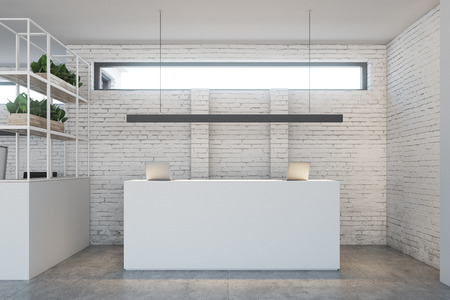 White reception table with two laptops is standing in a white brick wall office lobby under a narrow horizontal window. 3d rendering mock up Фото со стока