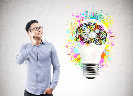 Portrait of a cheerful Asian businessman wearing a blue shirt, jeans and glasses and talking on his smartphone. Concrete background with a brain and gears inside a light bulb