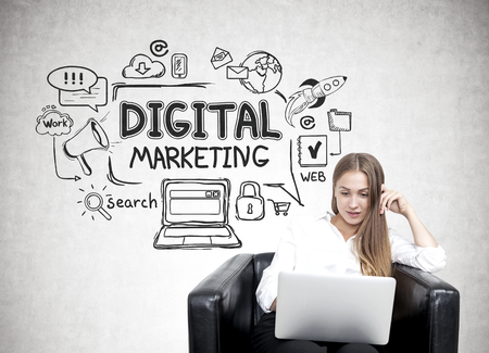 marketing online: Young businesswoman in a white blouse is sitting in an armchair with a laptop. There is a digital marketing sketch on a concrete wall behind her. Stock Photo