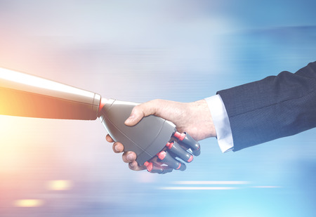 Close up of a businessman in a suit and a robot shaking hands. Blurred background. Concept of innovation in business. Toned image