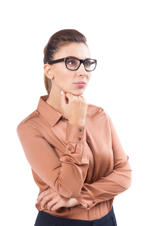 Isolated portrait of a pensive young woman with dark hair wearing glasses and a beige blouse. Concept of decision making.