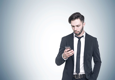Close up portrait of a young bearded businessman wearing a dark suit and looking at his smartphone screen. Concept of communication. Gray background. Mock up