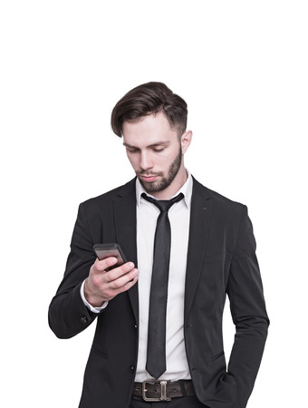 Isolated close up portrait of a young bearded businessman wearing a dark suit and looking at his smartphone screen. Concept of communication