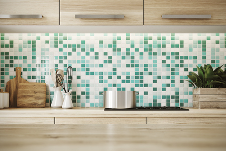 Close up of a light hardwood table surface in a kitchen with green and white mosaic walls, wooden consoles and a cooker. 3d rendering copyspace