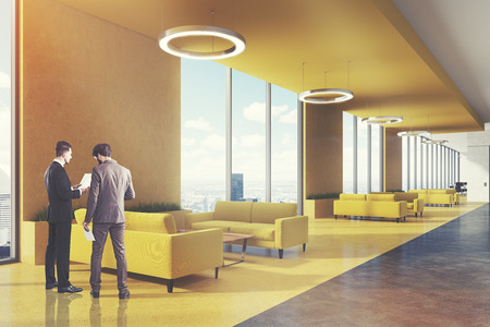 Office waiting area with yellow sofas, coffee tables, round ceiling lamps and loft windows. People. 3d rendering mock up toned image Stock Photo