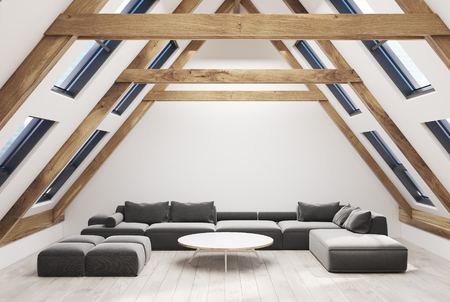 Attic living room interior with a pitched roof, white walls and a wooden floor. There is a large gray sofa and a narrow round coffee table. 3d rendering mock up