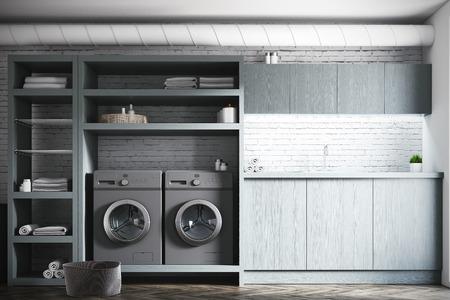 Moderner Waschkücheinnenraum mit Weiß- und Ziegelsteinwänden, graue hölzerne Konsolen und Regale und zwei graue Waschmaschinen. Spott der Wiedergabe 3d Standard-Bild - 87045082