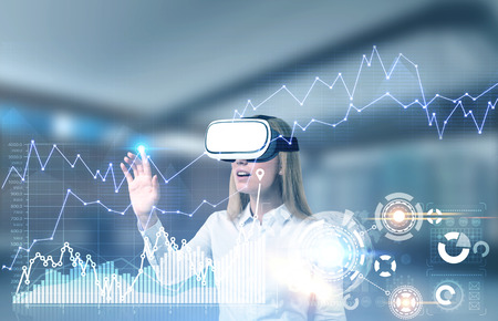Blonde young businesswoman in VR glasses interacting with graphs and HUD in a blurred office. Toned image double exposure mock up Elements of this image furnished by NASA