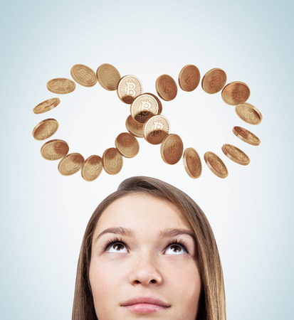 Close up of a young woman s head. She has fair hair and large beautiful eyes. She is looking at an infinity symbol made of bitcoins. 3d rendering Stock Photo