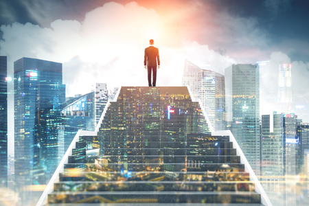 Rear view of a young businessman on the top of stairs. A magnificent modern city background. Night city in the foreground. Concept of a road to success. Toned image double exposure
