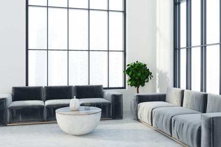 White living room interior with two black sofas, a round coffee table and a potted tree near a loft window. 3d rendering Stock Photo