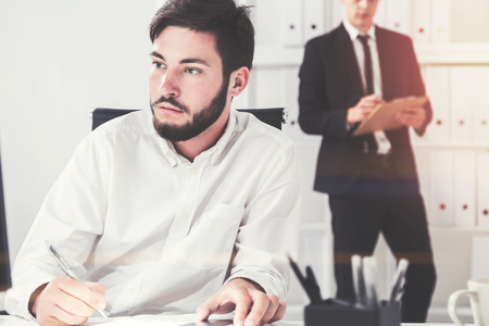 Two young and attractive businessmen working in a white office. Graphs and infographics. Toned image