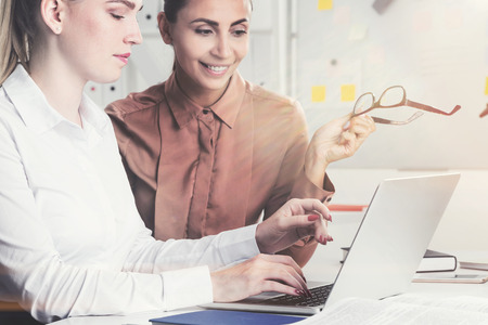 Side view of a blonde businesswoman discussing a project with her colleague in a white office. Toned image