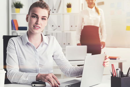 mobile marketing: Inspired young businesswoman is sitting at her laptop in a modern office. Her colleague is in the background. Toned image Stock Photo