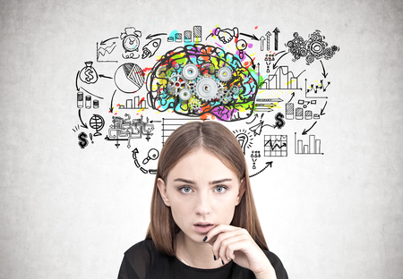 Portrait of a young woman wearing black and looking at the viewer with a hand near her face. Concrete wall background with a business plan sketch and a brain with gears
