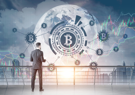 Rear view of a young bearded businessman wearing a black suit and a white shirt and holding a document looking at a bitcoin HUD hologram in a morning city sky. A balcony. Toned image double exposure