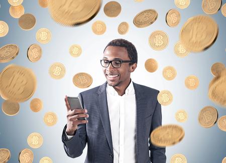 Retrato de un hombre de negocios afroamericano sonriente joven que lleva un traje y una camisa y que mira su pantalla del smartphone. Fondo gris, una lluvia bitcoin.