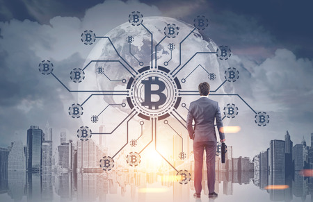 Rear view of a young businessman holding a suitcase looking at a bitcoin network hologram in a morning city sky