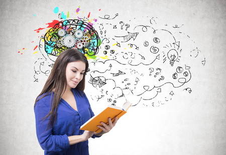 Portrait of a young smiling businesswoman wearing a blue blouse and reading an orange book. Gray background with arrows and questions marks and a brain with gears above her Stockfoto
