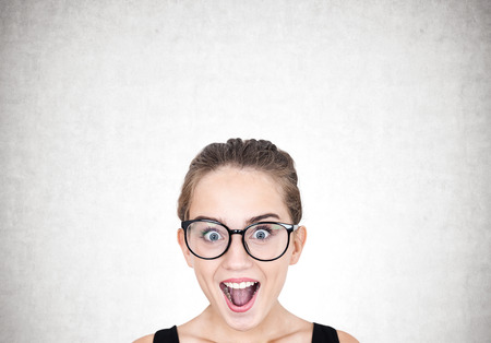 Close up portrait of a young astonished woman wearing round glasses and standing with an open mouth. Concrete background Stock Photo - 88804368