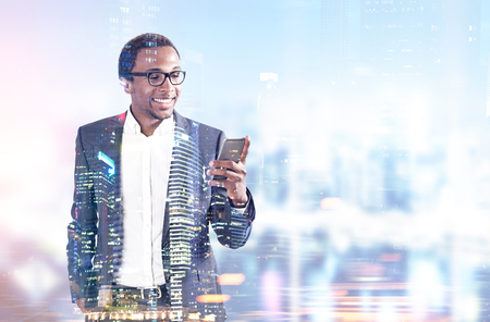 Smiling African American businessman in glasses looking at his smartphone screen and standing in his office, a cityscape. Toned image double exposure mock up