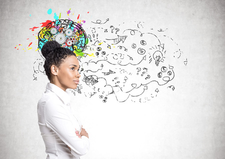 Portrait of a strong and independent African American woman wearing black and standing with her hands on the waist. Concrete wall with a brain with gears on it