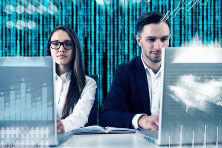 Young business couple working at their laptops. Glowing zeros and ones are falling behind them. Graphs. Double exposure toned image Elements of this image furnished by NASA Stock Photo