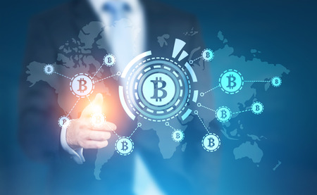 Businessman with a glowing finger pointing at a bitcoin HUD hologram in the air. Elements of this image furnished by NASA. Toned image double exposure